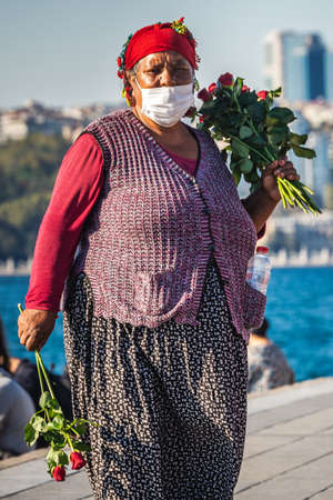 Woman cells roses near Maiden's Tower. IT is a tower lying on a small islet located at the southern entrance of the Bosphorus in Istanbul, Turkey. Istanbul, Turkey - October 01 2020. Publikacyjne