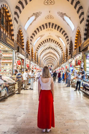 Pretty young woman in the red dress shopping for handmade pillows, bags, carpets and souvenirs in famous Grand Bazaar. Istanbul, Turkey - September 30 2020.