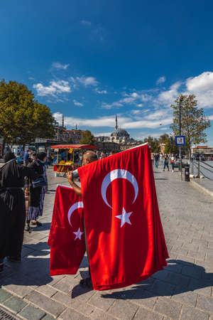 Traditional Turkish Flag seller in the center of crowded Eminonu square in Istanbul, Turkey. Istanbul, Turkey - September 30 2020. Publikacyjne