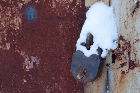 Old, rusty padlock coated by snow, gates Stock Photo - 4448765