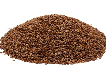 Heap buckwheat croups, disposit on white background photo