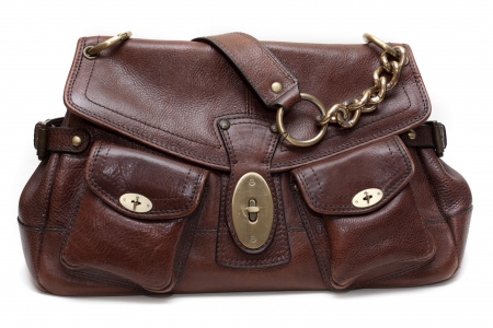 Beautiful brown leather feminine bag with golden chain-handle and lock insulated on white background photo