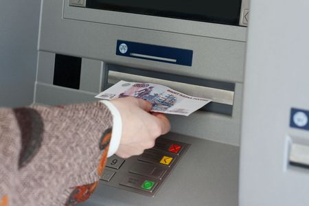 Girl gets 500 roubles from bank terminal Stock Photo - 4849166