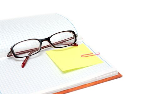 Spectacles on note pad with yellow bookmark and rose staple Stock Photo - 4963956
