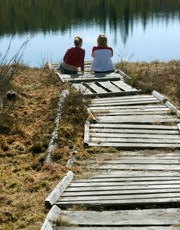 holistic view: Two girls sit on pier north lake