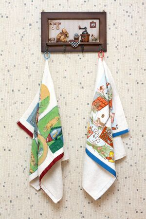 Dishtowels hung on wooden hatrack on background sulphur wallpaper photo