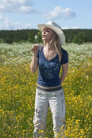Beautiful making look younger girl in field with yellow flower photo