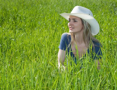Beautiful girl smiles in white hat on background of the green herb Stock Photo - 5241784
