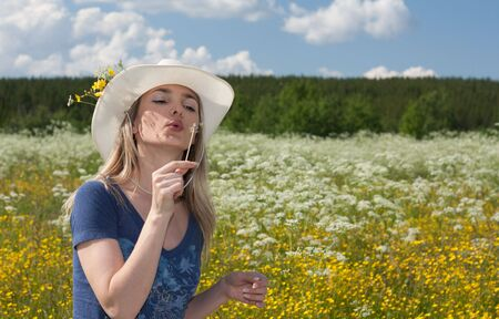 Beautiful girl blows on dandelion in field with yellow flowers in white hat Stock Photo - 5245986
