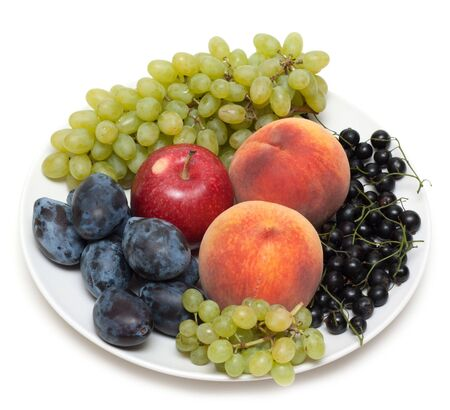 Still life, plate with fruit peaches grape discharges currant photo