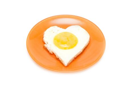 Fried egg in form heart on plate photo