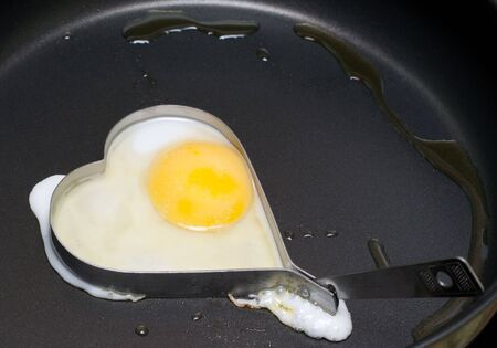 Fried egg on pan in iron form heart photo