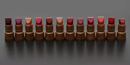 Small tubeses lipstick on dark gray background photo
