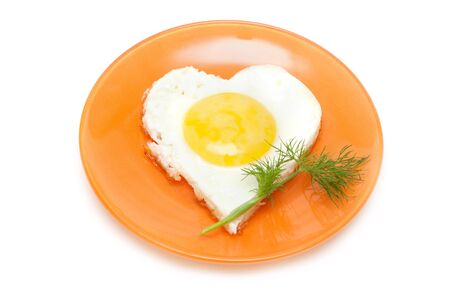 Fried egg in form heart on plate with dill photo