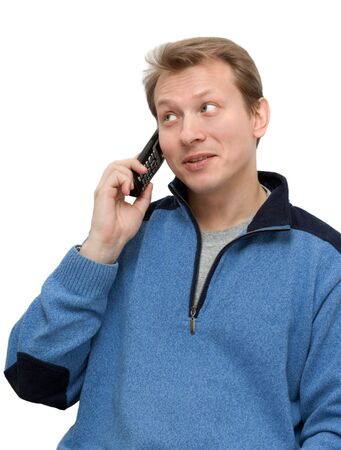 telephonic: Man in blue sweater speaks on telephone on white background