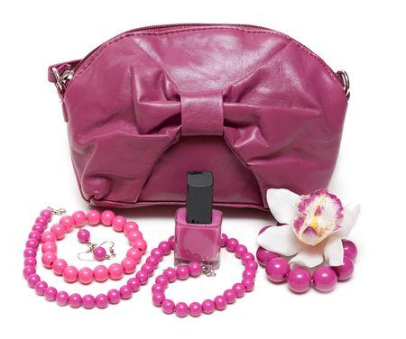 Violeta bolsa femenino, el collar y el maquillaje sobre fondo blanco Foto de archivo