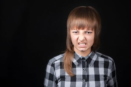 hiss: Young beautiful girl in plaid shirt snarls on black background