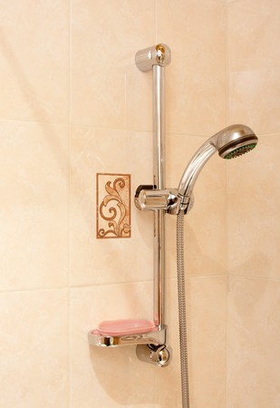 Bathroom room chromed shower and red soap on background beige ceramic wall photo
