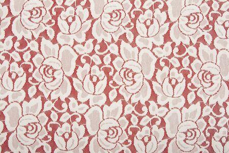 Witte kant met bloemmotief op rode achtergrond Stockfoto