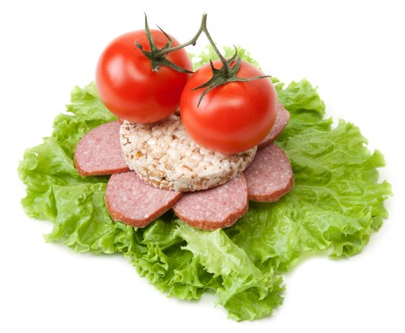 Sandwich with sausage from small loaf of bread, tomatoes and salad photo