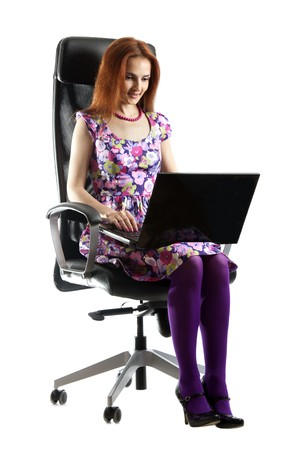 Beautiful girl in easy chair with computer on white background photo