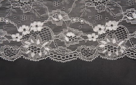 Decorative white lace on insulated black background photo