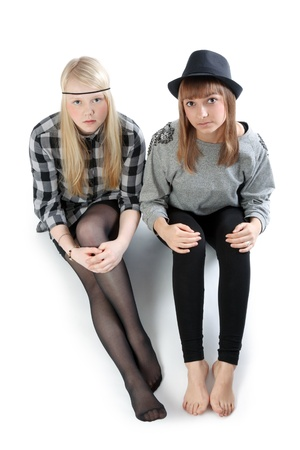 Two beautiful young girls sit on floor photo