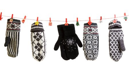 Winter knitted gloves hang on the Christmas lights in the clothes pins photo