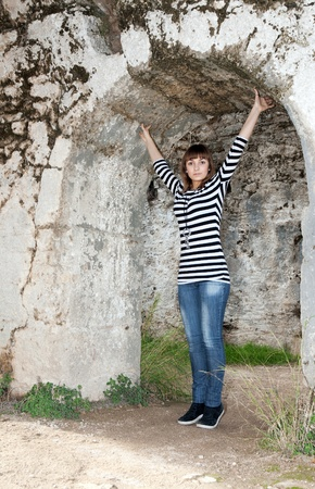 Young girl in jeans in an arch in the ruins photo