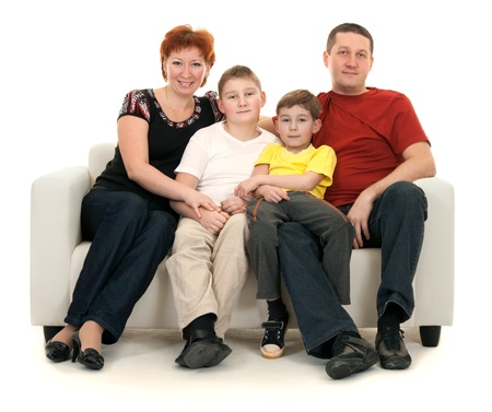 Family of four on a sofa on a white background Stock Photo - 8590375