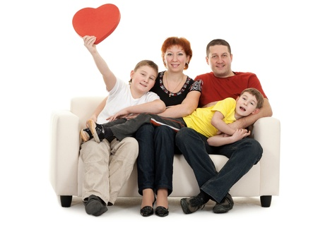 family on couch: Family silit on the couch in the hands of a red decorative heart Stock Photo