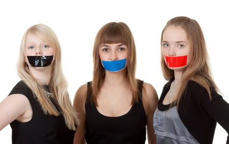 Three beautiful girls with their mouths taped with tape photo