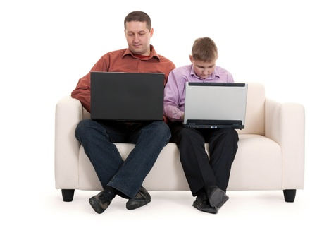 Father and son sitting on the couch with laptops photo