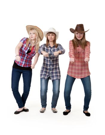 imitate: Three girls in hats imitate horse riding on a white background Stock Photo