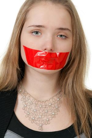 imbavagliare: bella ragazza con la bocca chiusa con nastro rosso
