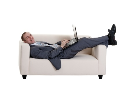businessman lying on the couch with a laptop on a white background photo