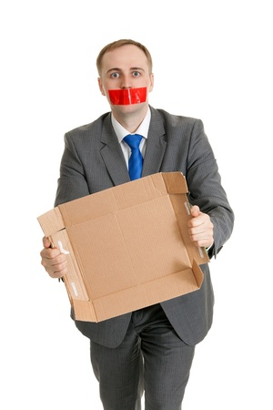 Businessman with his mouth sealed with red tape and cardboard in their hands photo