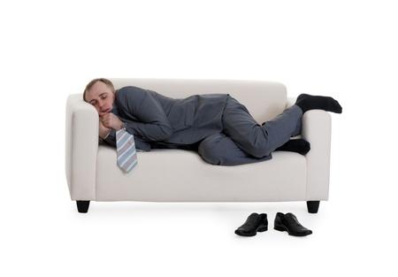 businessman sleeping on a sofa on a white background