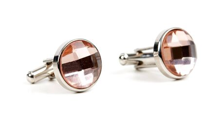 pair of platinum cufflinks with a pink stone isolated on white background photo