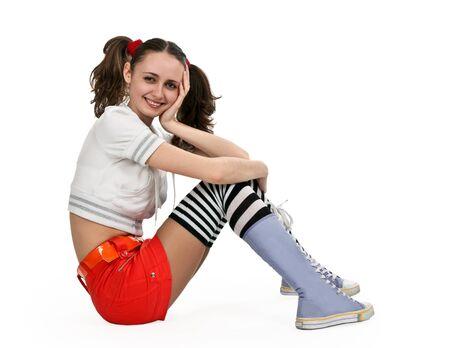 girl in striped socks and orange mini skirt sitting on a white floor photo