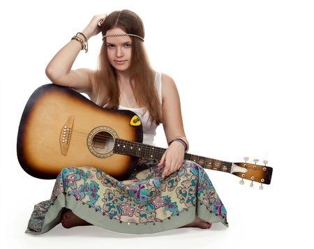 hippie girl with a guitar sitting on a white floor photo