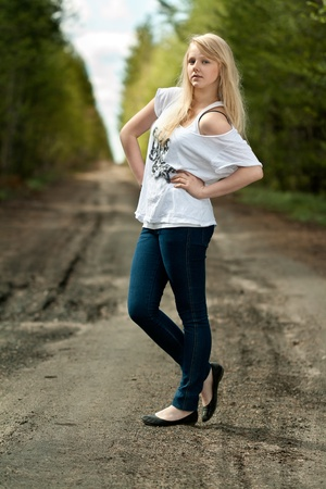 off the shoulder: beautiful blonde in a white T-shirt off shoulder on the road in the woods Stock Photo
