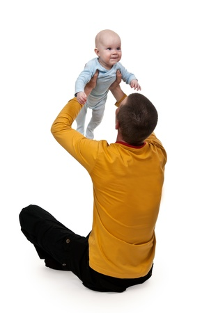 tosses: Dad is sitting on the floor and tosses baby Stock Photo