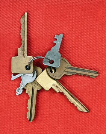 old keys from the door isolated on red background photo