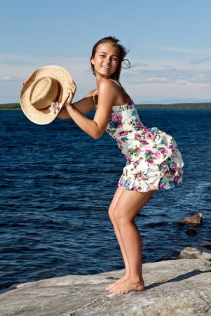 girl with a straw hat standing on a rock by the lake Stock Photo - 10061603