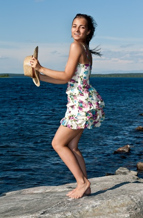girl with a straw hat standing on a rock by the lake Stock Photo - 10061554