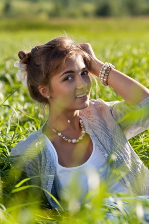 portrait of a beautiful girl in the green grass photo