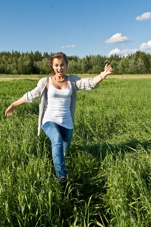 beautiful young girl goes on the green grass Stock Photo - 10120569