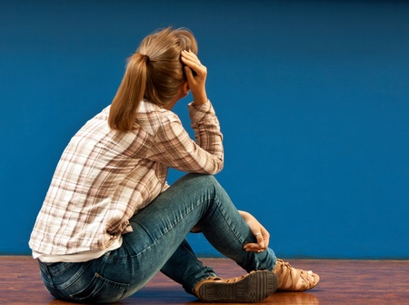 Offended by a girl sitting on the floor turned to the blue wall photo