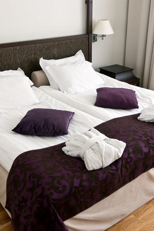 bedding indoors: hotel room, bed, pillows and neatly folded robes Stock Photo